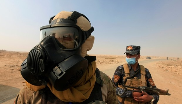 Iraqi forces wear protective masks after winds brought fumes from a nearby sulfur plant, at Mosul in