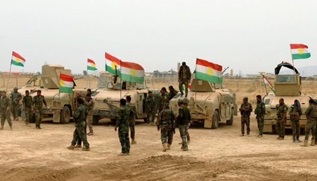 Kurdish military vehicles are seen during a battle with Islamic State militants