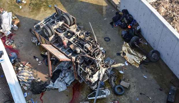 Turkish police forensic experts examine the wreckage of a truck, carrying migrants, after it crashed