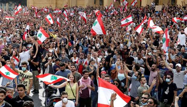 Demonstrators hold Lebanese flags as they gather during a protest over deteriorating economic situat