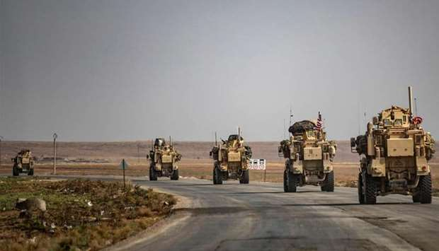US military vehicles drive on a street in the town of Tal Tamr