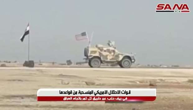 A military vehicle bearing a U.S. flag travels past a Syrian flag flying by a roadside in Tel Tamer,