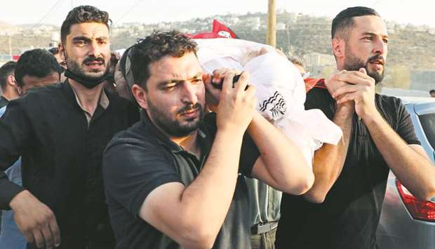 Palestinian mourners carry the body of 18-year-old Amer Abdel-Rahim Sanouber, who died following a c