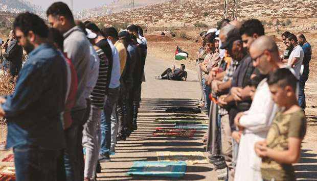 A Palestinian protester waves a national flag, as others perform the Friday prayers during a demonst