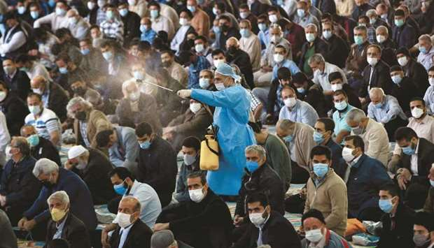 A municipal worker sprays disinfectant as mask-clad Iranians gather in a mosque in the capital Tehra