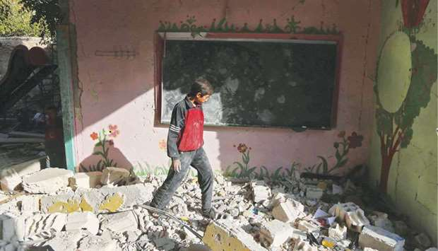 A Syrian boy walks amid the rubble inside his damaged school in the besieged rebel-held Eastern Ghou