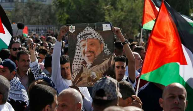Hundreds of Palestinians gather with national flags in front of the tomb of late Palestinian leader