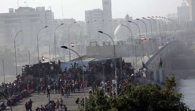 Iraqi demonstrators are seen at Sinak Bridge during the ongoing anti-government protests, in Baghdad