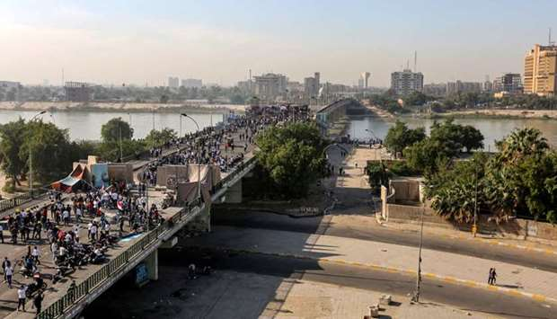 Iraqi anti-government protesters gather at a sit-in near barricades over al-Sinek bridge connecting