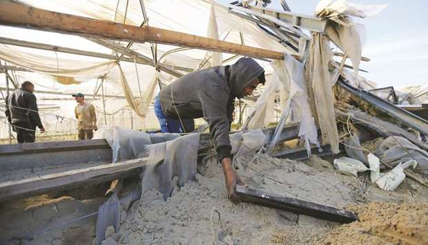 A Palestinian man inspects the damage at the site of an Israeli air strike in the southern Gaza Stri