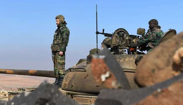 Members of the Syrian government forces stand on a tank in Jabal al-Hass
