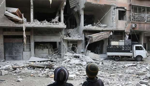 Syrian children look at a building that was damaged in a missile attack on the rebel-held besieged t