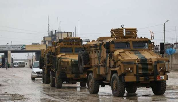 Turkish military vehicles ride at the Bab el-Salam border crossing between the Syrian town of Azaz a