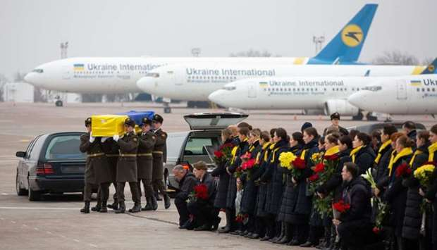 Soldiers carry a coffin containing the remains of one of the eleven Ukrainian victims of the Ukraine