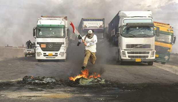 An Iraqi protester jumps over burning tyres, blocking an international highway in the southern city