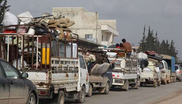Syrians arrive in trucks transporting their belongings to Hazano in the northern countryside of Idli