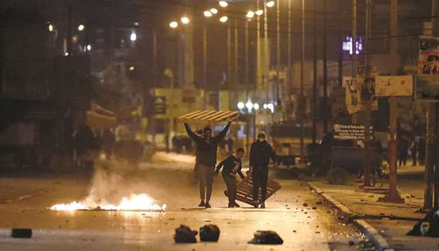 Protesters block a street during clashes with security forces in the Ettadhamen city suburb on the n
