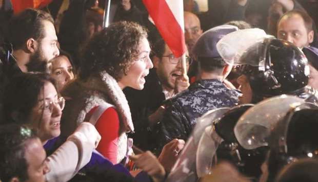 Lebanese anti-government protesters scuffle with riot police on the eastern end of the Ring bridge t