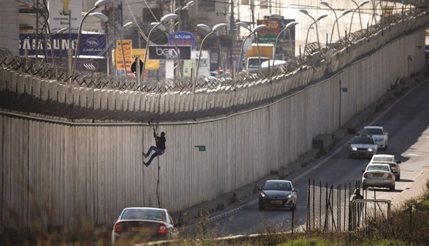 A Palestinian Man Uses A Rope To Climb Over A Section Of Israelu0027s  Controversial Barrier That Separates The West Bank City Of Al Ram From East  Jerusalem ...