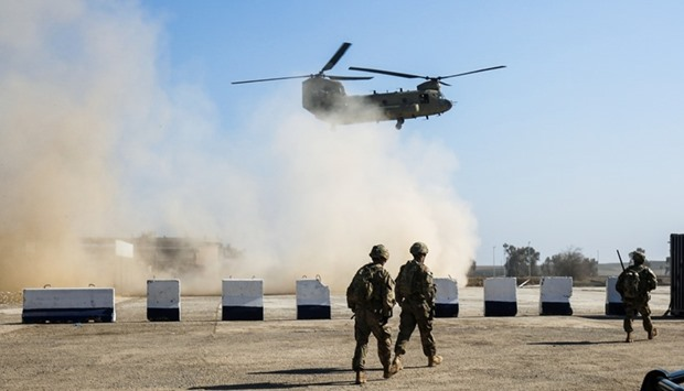 US troops walk as a US C-47 Chinook helicopter flies over the village of Oreij, south of Mosul