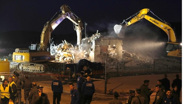 Diggers under the supervision of Israeli forces destroy a house in the Jewish settlement of Ofra in