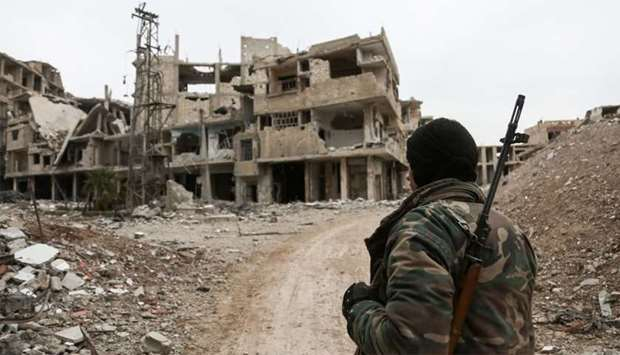 A Syrian fighter carrying a sniper rifle walks down a street full of damaged and partially destroyed
