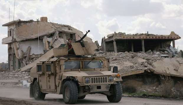 A fighter from the Syrian Democratic Forces (SDF) rides on a vehicle in the village of Baghouz, Deir
