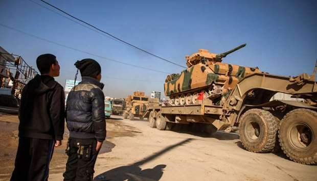 A Turkish military convoy of tanks and armoured vehicles passes through the Syrian town of Dana, eas
