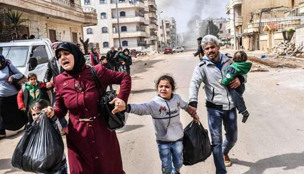 Civilians run cover from explosions in the city of Afrin in northern Syria  after Turkish forces and