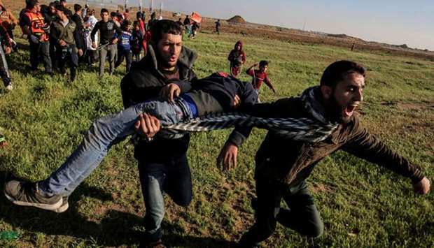 Palestinian men carry an injured protester at the border fence with Israel east of Gaza City on Marc
