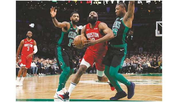 Houston Rockets guard James Harden drives between Boston Celtics guard  Kyrie Irving (left) and guard Marcus Smart during the first quarter at TD  Garden. 9bf8a706e