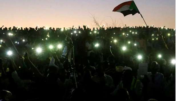 Sudanese demonstrators use their mobile phone torches as lamps as they attend a mass anti-government