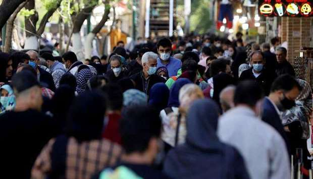 FILE PHOTO: Iranians wearing protective face masks against the coronavirus walk in a crowded area of