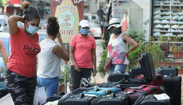 Women wearing face masks look at luggage displayed for sale in Dora, Lebanon.