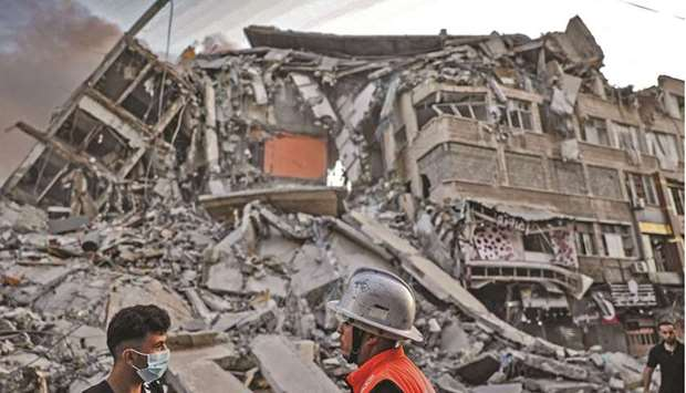 Rescuers and people gather in front of the debris of Al-Sharouk tower that collapsed after being hit