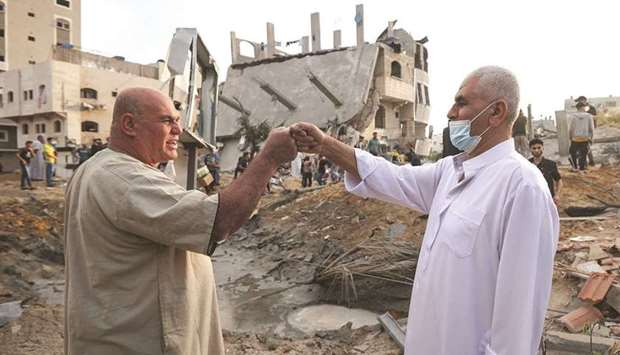 Palestinian men exchange Eid al-Fitr holiday wishes in front of a destroyed building in the northern