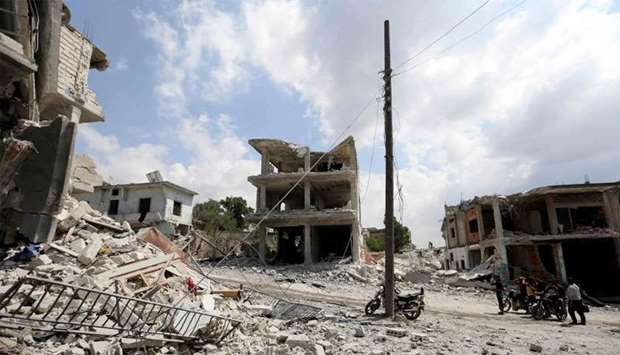 People gatehring next to a damaged building in the town of Ihsim, in Syria's Idlib region