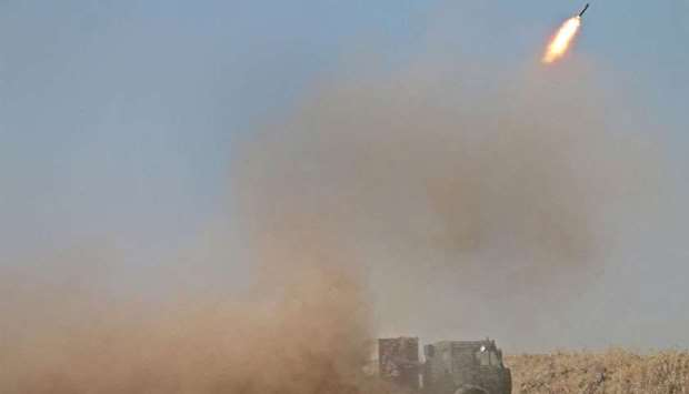 Syrian rebels fire rockets during clashes with regime forces advancing toward the town of al-Hara in