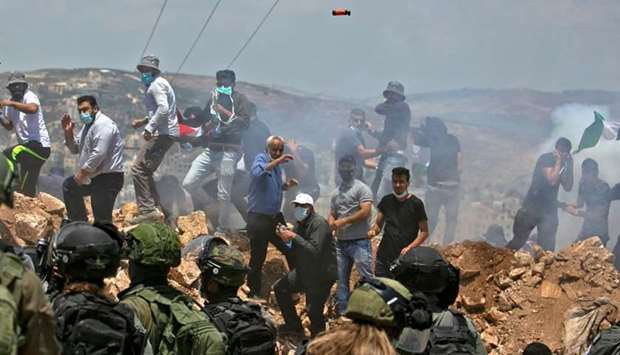 Palestinian demonstrators and Israeli forces clash during a protest against Jewish settlements and I