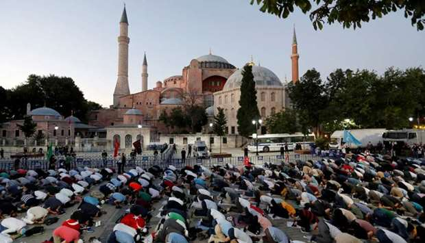 Muslims gather for evening prayers in front of the Hagia Sophia, after a court decision that paves t