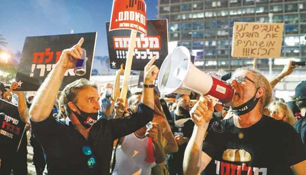 Israelis lift placards and chant slogans during a demonstration in Rabin Square in Tel Aviv yesterda