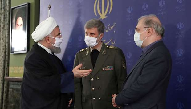 Iranian President Hassan Rouhani and Iranian Defense Minister Brigadier General Amir Hatami, wearing