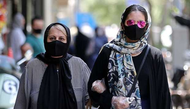 Iranian women wearing protective masks due to the COVID-19 pandemic, walk along a street in the capi