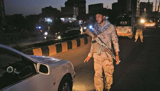 A security personnel stops a vehicle at a check point in Herat yesterday, as a night curfew was impo