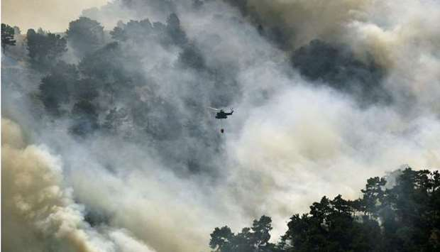 A Lebanese army helicopter drops water on a forest fire in the Qubayyat area of northern Lebanon's r