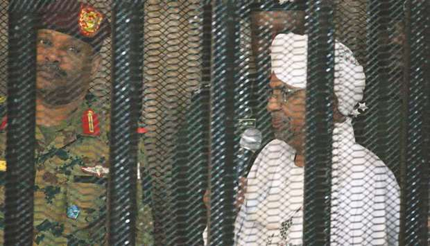 Omar al-Bashir stands in a defendant's cage during the opening of his corruption trial in Khartoum y