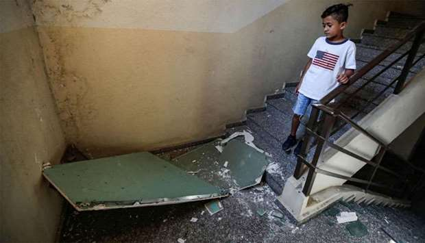 A boy walks past debris in a building housing a media centre of the Lebanese group Hezbollah that wa