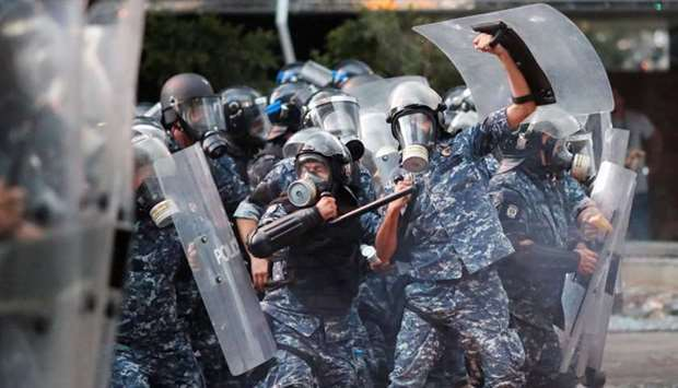 Police officers form a line during anti-government protests that have been ignited by a massive expl