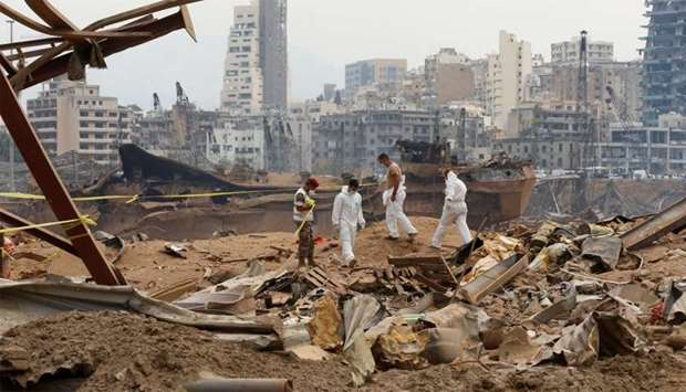 Members of forensic team walk near rubble at the site of Tuesday's blast, at Beirut's port area, Leb