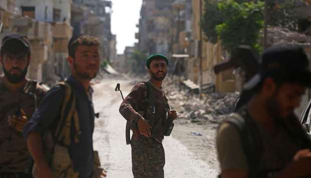 Members of the Syrian Democratic Forces walk in the former Islamic State (IS) stronghold of Raqqa